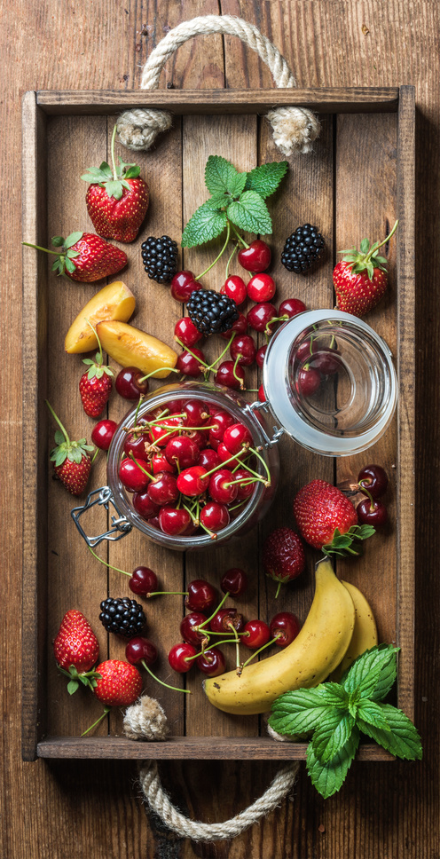 Healthy summer fruit variety. Sweet cherries, strawberries, blackberries, peaches, bananas and mint leaves in rustic wooden tray. Top view